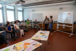 Participants listen to talk, with table of post-it notes in foreground