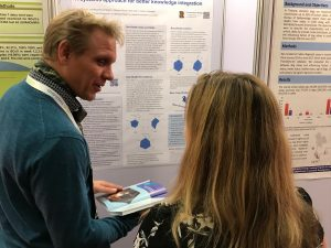 Simon Ruegg explains his poster and shows the NEOH handbook to a delegate